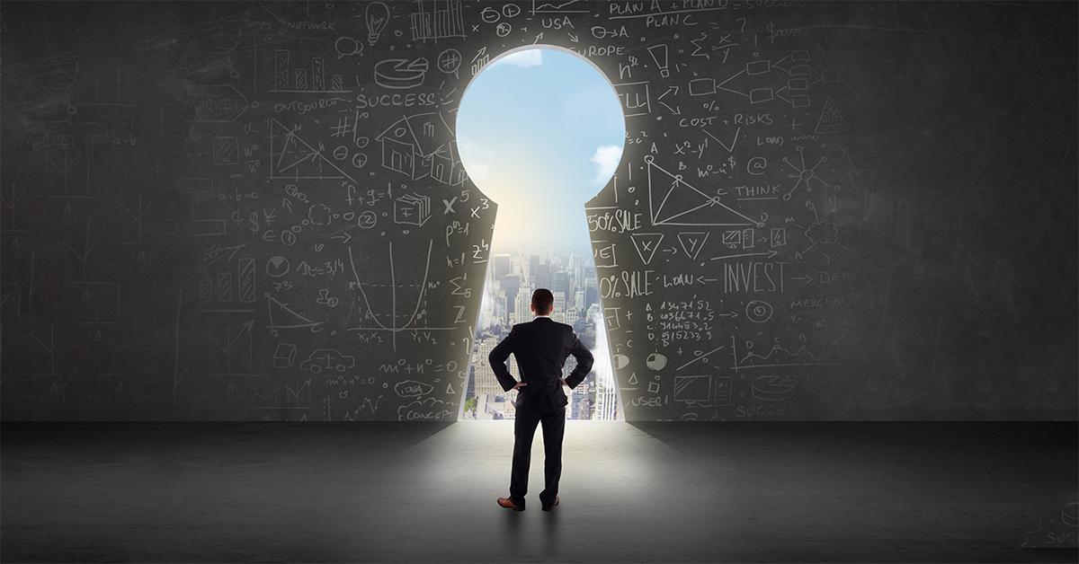 Businessman a world of opportunities through a keyhole